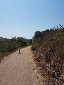 Bambini che cammino sul sentiero sterrato per raggiungere una spiaggia della Sicilia