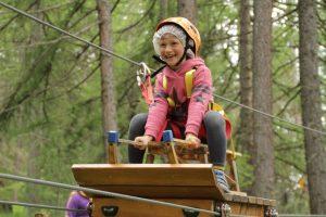 bambina scende con slitta in un parco avventura