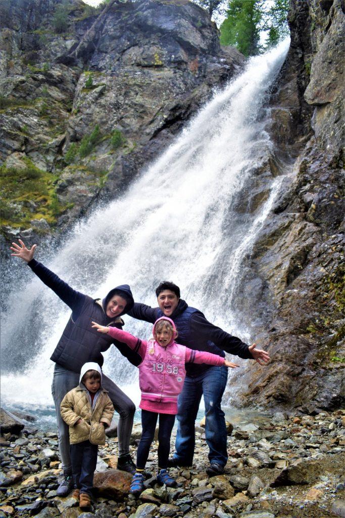 Una famiglia davanti alla cascata della Val Nera a Livigno