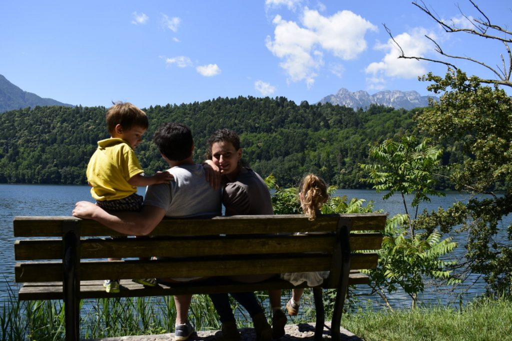 Famiglia in relax su una panchina in riva al Lago di Levico