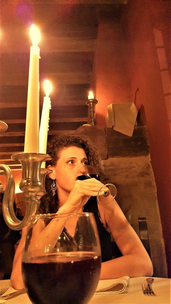 Donna con calice di vino rosso che cena a lume di candela