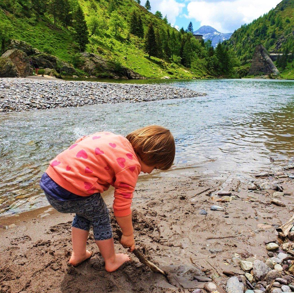 bambina gioca con la sabbia del Lago di Gleno in Valle di Scalve