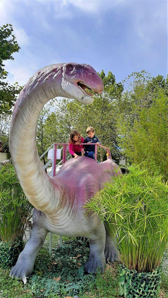 bambini cavalcano un dinosauro al Dinosaurs Park