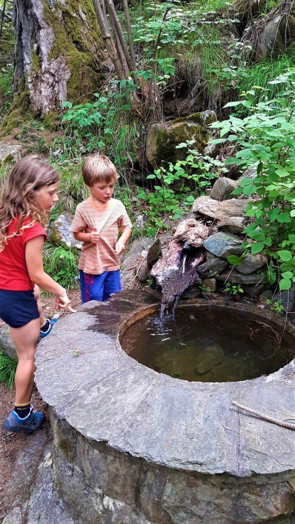Bambini si dissetano da una fontana in pietra a Chiesa in Valmalenco