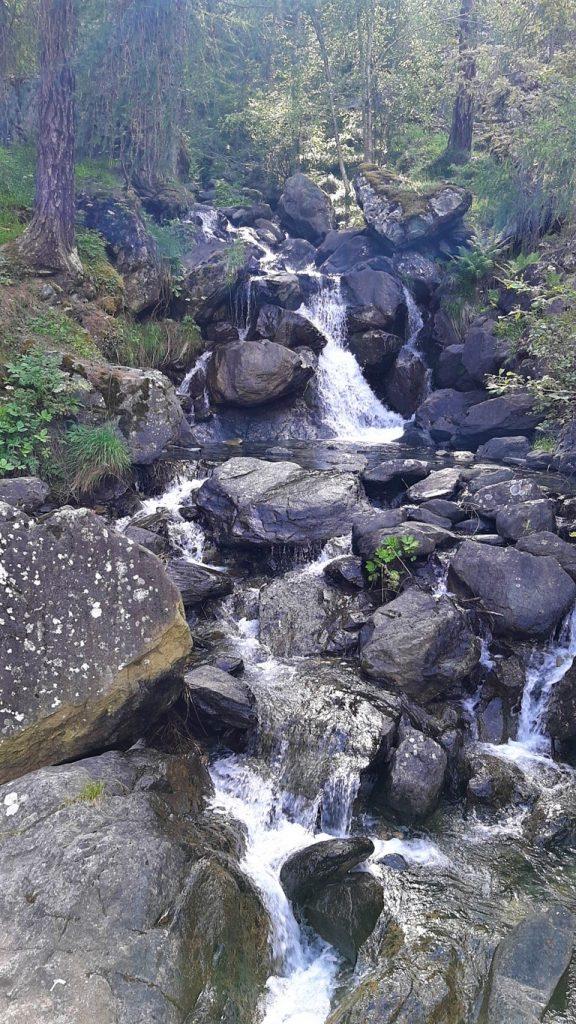 Un torrente che scende dalla montagna tra le rocce a Chiesa in Valmalenco