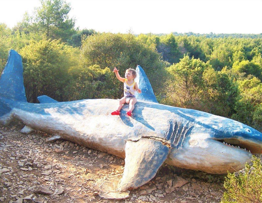 bimba seduta su installazione del sentiero dei dinosauri a Kamenjak